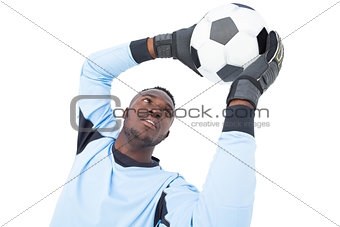 Goalkeeper in blue making a save