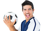 Happy football player in blue holding the ball
