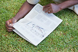 Man relaxing in his garden reading newspaper