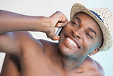 Smiling man talking on phone by the pool