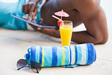 Shirtless man using his tablet pc with towel and sunglasses in foreground
