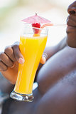 Shirtless man drinking orange cocktail