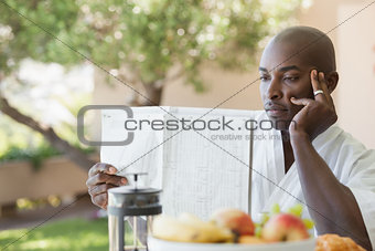 Man in bathrobe reading paper and having breakfast on terrace