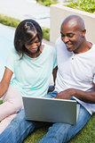 Happy couple using laptop together outside