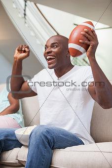 Bored woman sitting next to her boyfriend watching sport