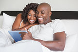 Happy couple using tablet in bed