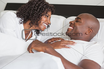 Happy couple laughing together in bed