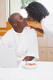 Pretty woman in bathrobe kissing partner at table