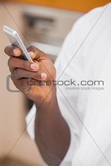 Man in bathrobe holding smartphone
