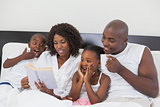 Family relaxing together in bed reading book