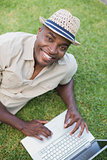 Smiling man relaxing in his garden using laptop