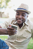 Smiling man relaxing in his garden texting on phone