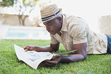 Smiling man relaxing in his garden reading newspaper