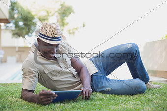 Smiling man relaxing in his garden using tablet pc