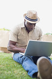 Handsome man relaxing in his garden using laptop