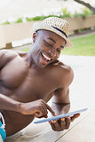 Handsome shirtless man using tablet pc poolside