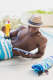 Handsome shirtless man using tablet pc poolside with cocktail