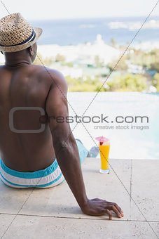 Man in swimming trunks relaxing poolside