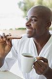 Handsome man in bathrobe having breakfast outside