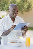 Handsome man in bathrobe using tablet at breakfast outside