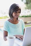 Pretty woman sitting outside using laptop
