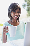Pretty woman sitting outside using laptop having coffee