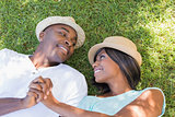 Happy couple lying in garden together on the grass