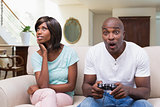 Bored woman sitting next to her boyfriend playing video games