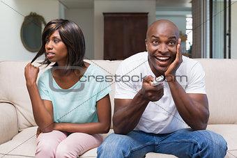 Bored woman sitting next to her boyfriend watching tv