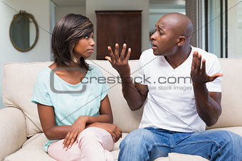 Unhappy couple having an argument on the couch