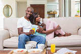 Happy couple relaxing on the couch with breakfast