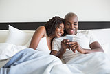 Happy couple cuddling in bed with smartphone