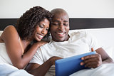 Happy couple cuddling in bed with tablet pc
