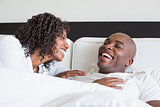 Happy couple cuddling in bed and laughing