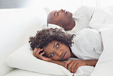 Annoyed woman lying in bed with snoring boyfriend