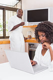Pretty woman in bathrobe using laptop at table with partner in background