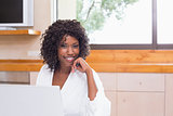 Pretty woman in bathrobe using laptop at table