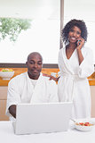Happy couple in bathrobes in the kitchen using technology