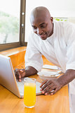 Happy man in bathrobe using laptop at table
