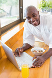 Happy man in bathrobe using laptop at breakfast