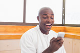 Happy man in bathrobe sending a text