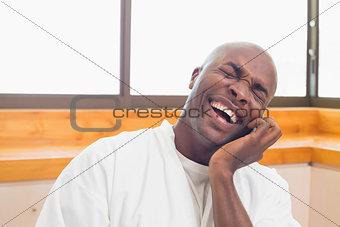 Laughing man in bathrobe talking on phone