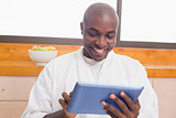 Happy man in bathrobe using tablet pc
