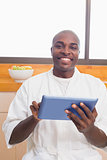 Happy man in bathrobe using tablet pc