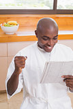 Happy man in bathrobe reading newspaper