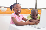 Cute siblings using laptop together