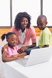 Cute siblings using laptop together with mother