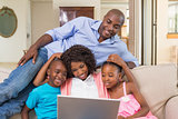 Happy family relaxing on the couch using laptop