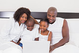 Happy family using laptop together in bed