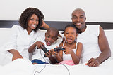 Happy family playing video games together in bed